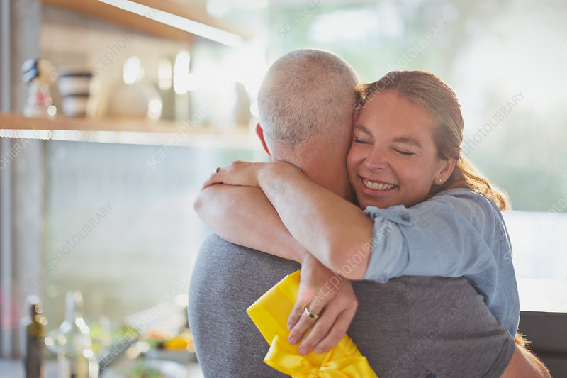 Happy couple hugging in kitchen