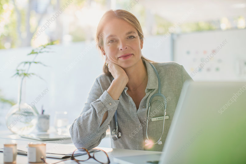 Portrait confident female doctor working at laptop