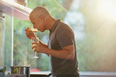 Man drinking white wine and cooking at stove