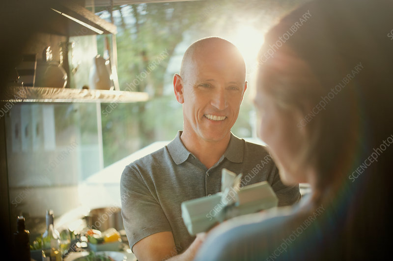 Smiling husband giving gift to wife