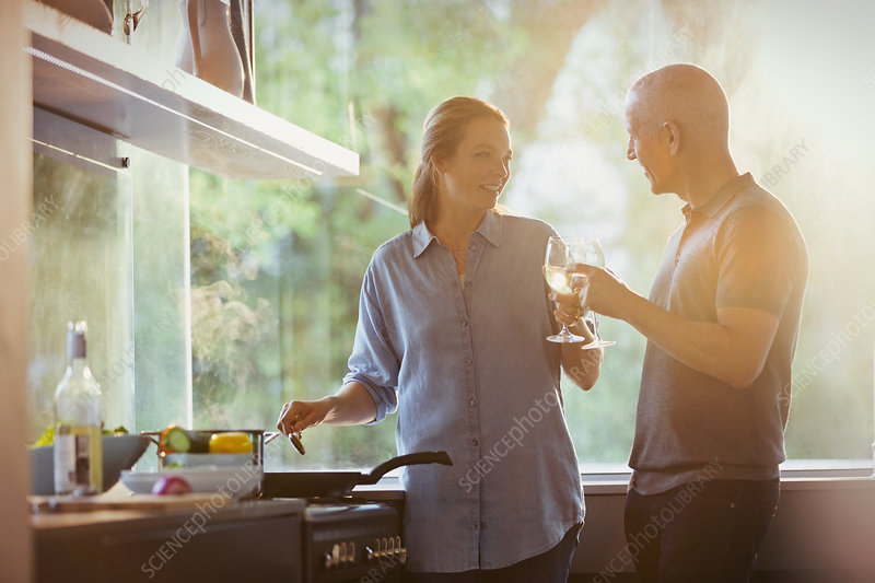 Couple toasting white wine glasses, cooking