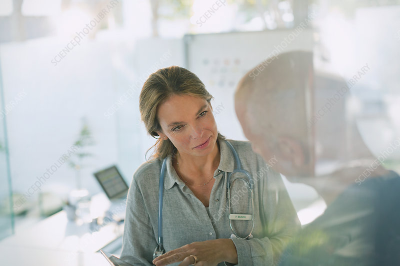 Female doctor with tablet talking to patient