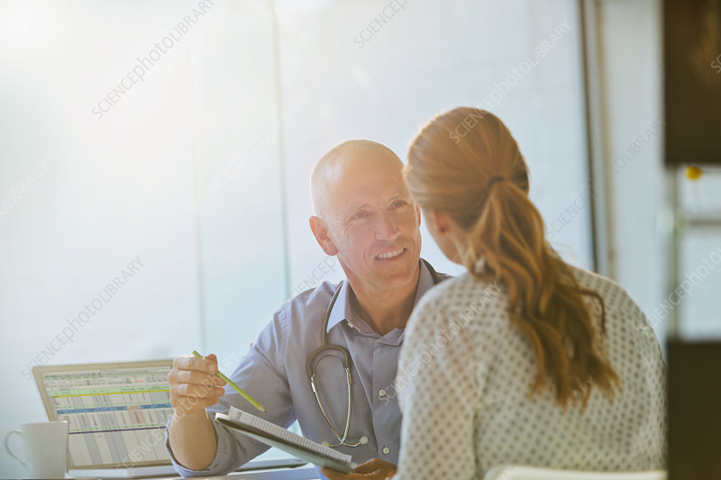 Male doctor discussing brochure with patient