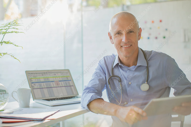 Portrait smiling male doctor with digital tablet
