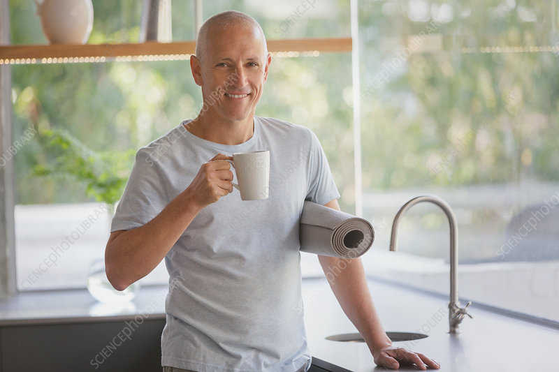 Portrait mature man with yoga mat drinking coffee