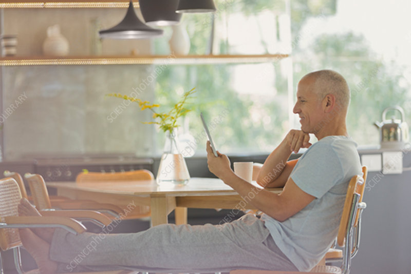Mature man relaxing, using tablet with feet up