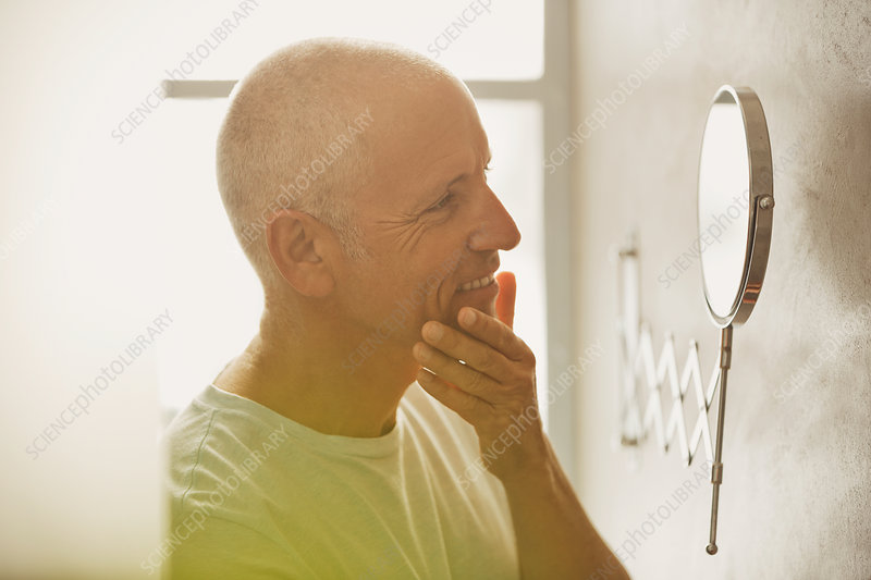 Mature man looking at skin in magnification mirror