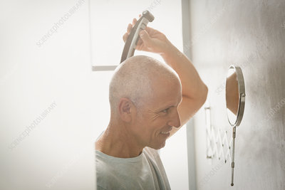 Mature man shaving head with electric razor