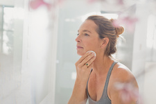 Mature woman applying makeup in bathroom mirror
