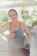 Portrait mature woman with yoga mat drinking juice