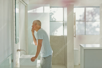 Mature man touching face at bathroom mirror