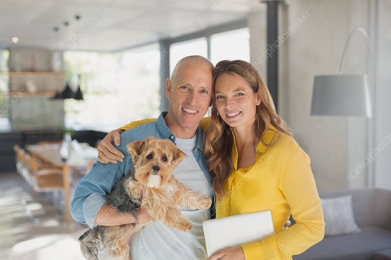 Portrait smiling mature couple hugging with dog