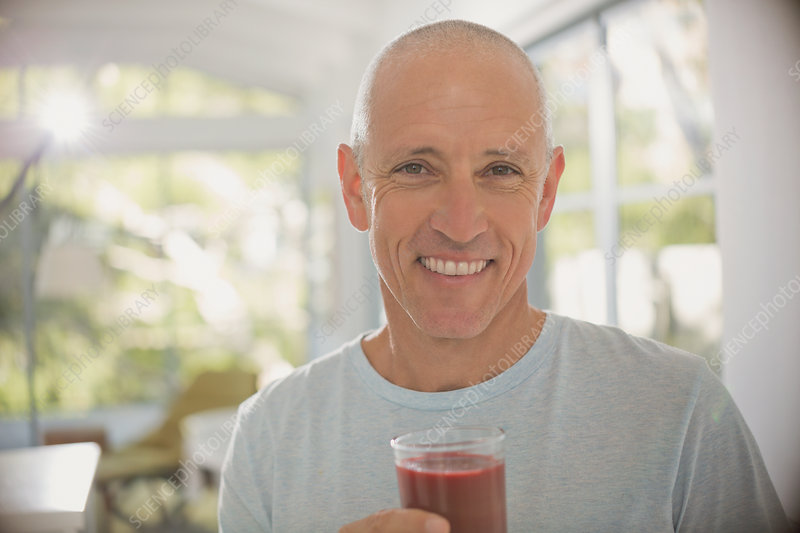 Mature man drinking healthy fruit smoothie
