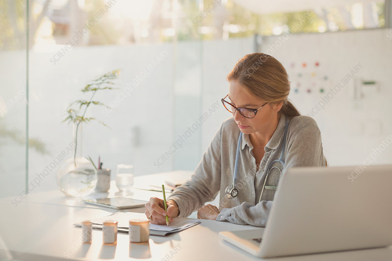 Female doctor writing prescriptions at desk