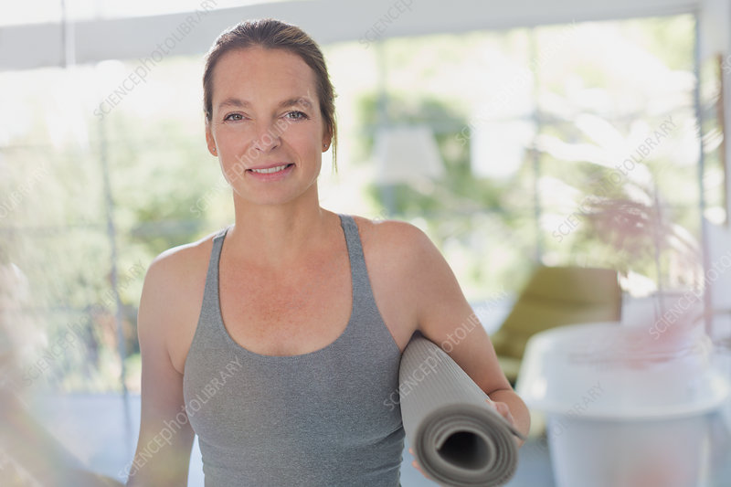Portrait smiling mature woman holding yoga mat