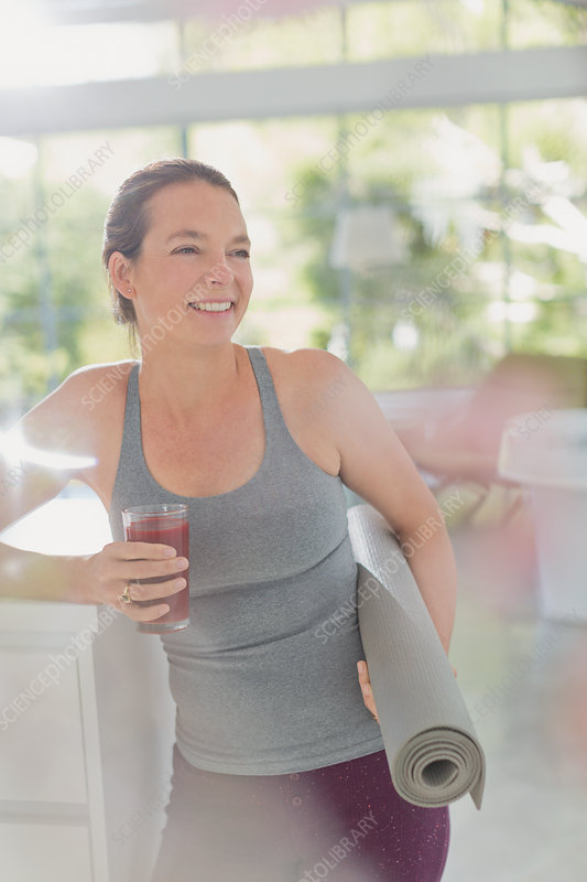 Woman with yoga mat drinking smoothie