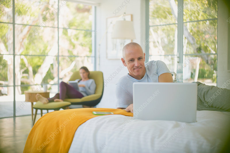 Mature couple relaxing, using laptop and tablet