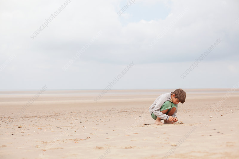 Boy playing in sand on overcast summer beach