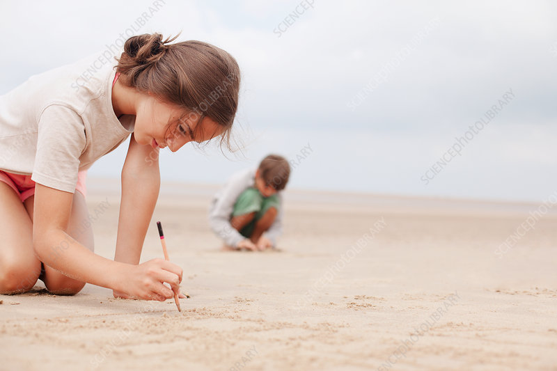Girl with stick writing in sand on summer beach