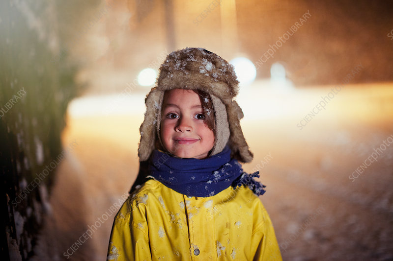 Portrait boy standing in snowy road