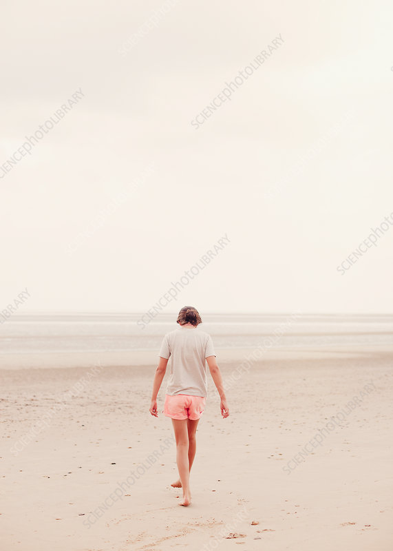 Teenage girl walking in sand