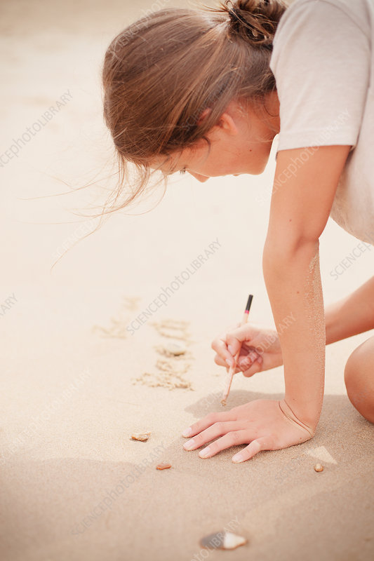 Teenage girl with stick writing in sand