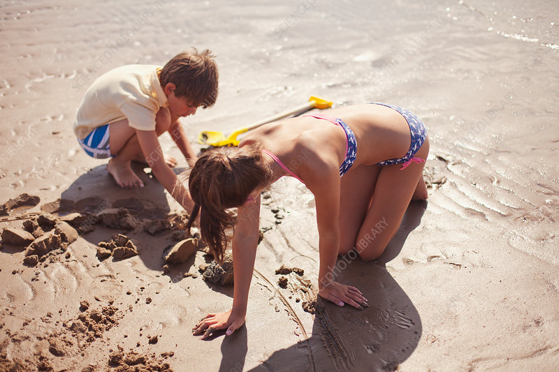 Brother and sister playing in wet sand