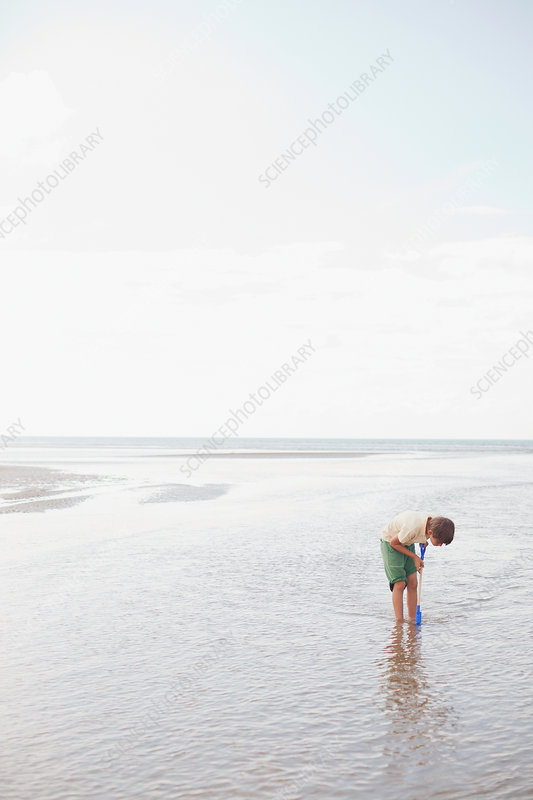 Boy with shovel playing in ocean surf