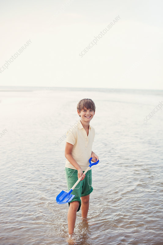 Portrait boy with shovel in ocean surf