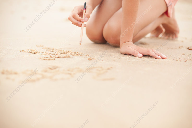 Girl with pencil writing in sand on summer beach