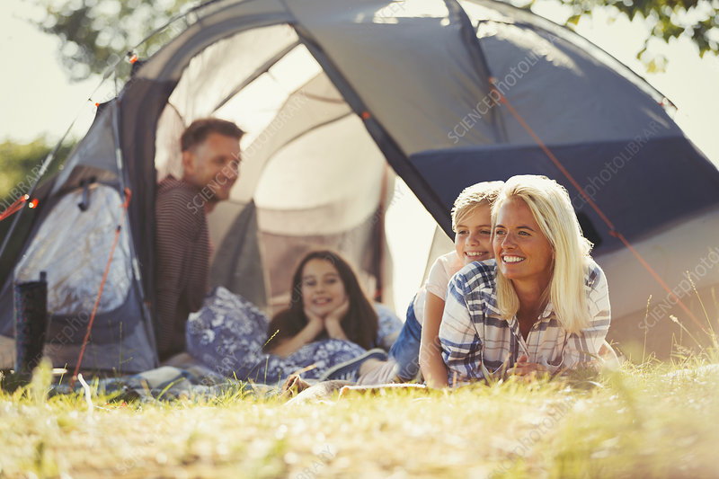 Smiling family relaxing outside tent