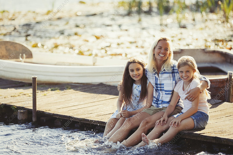 Portrait happy mother and daughters on dock