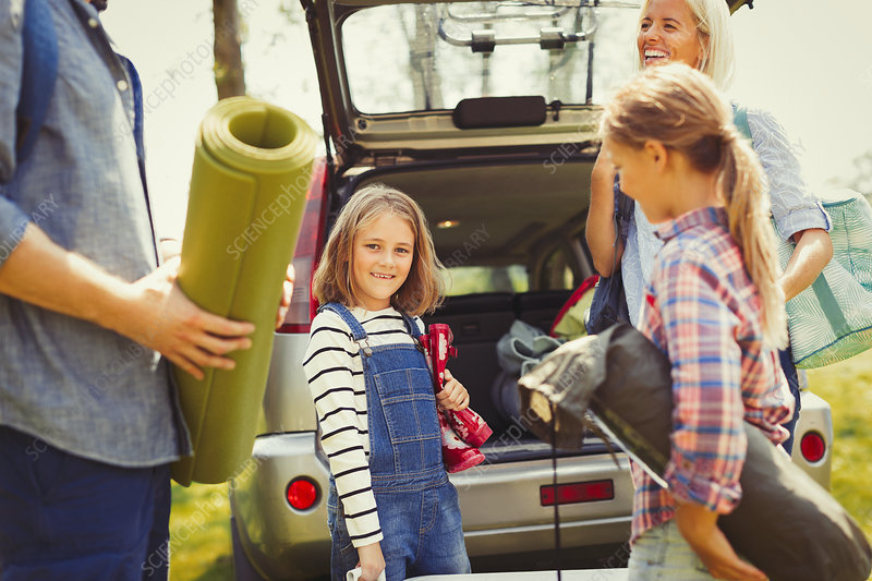 Portrait girl with family unloading car