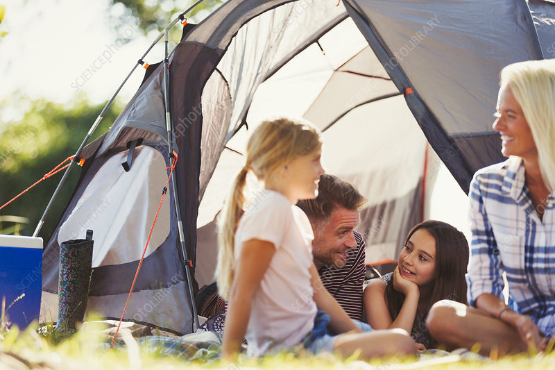 Smiling family talking and relaxing outside tent