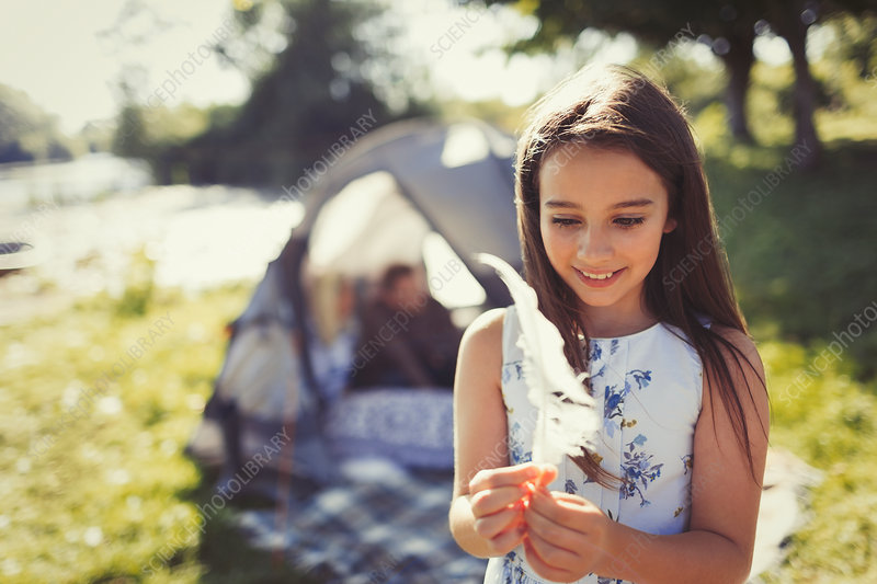 Smiling girl holding white feather