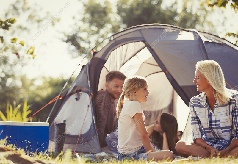 Family talking and relaxing outside tent