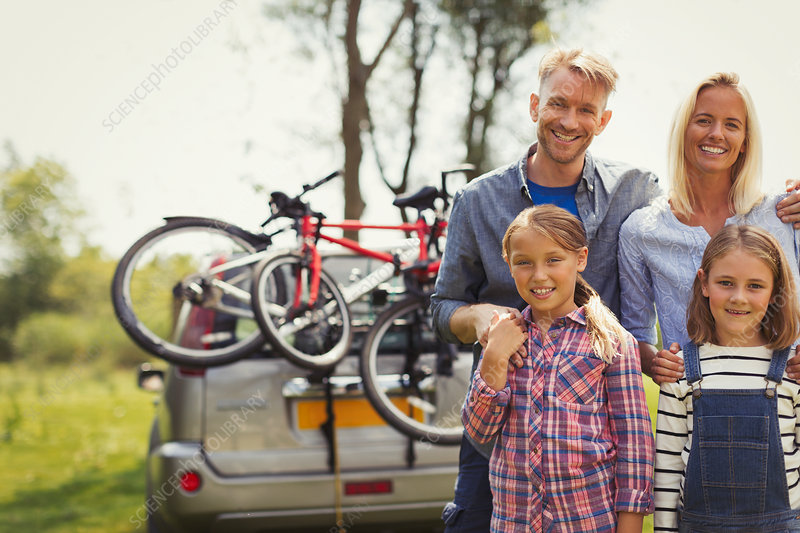 Portrait family near car with mountain bikes