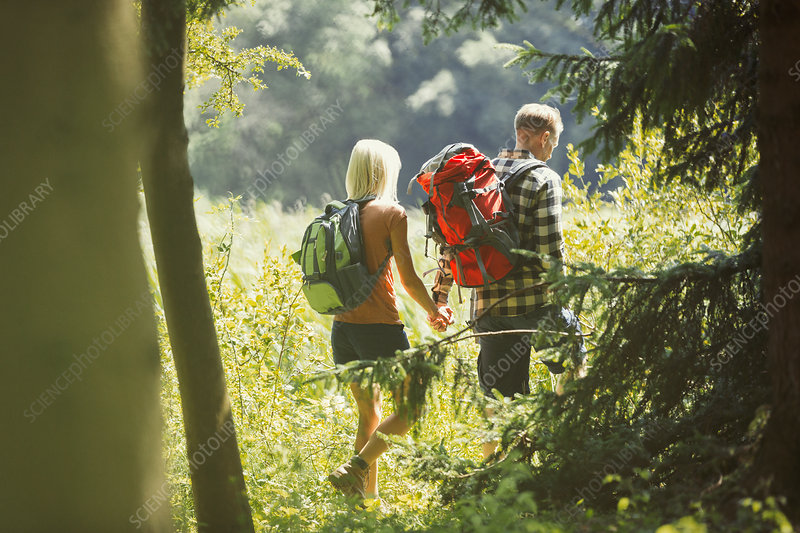 Couple with backpacks holding hands hiking