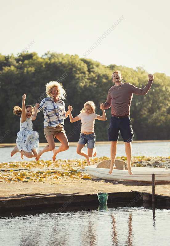 Portrait playful family jumping on lake dock