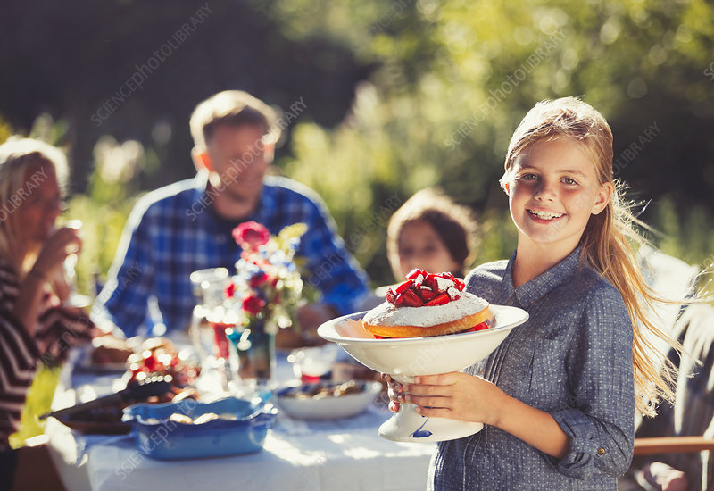 Portrait girl serving strawberry cake to family