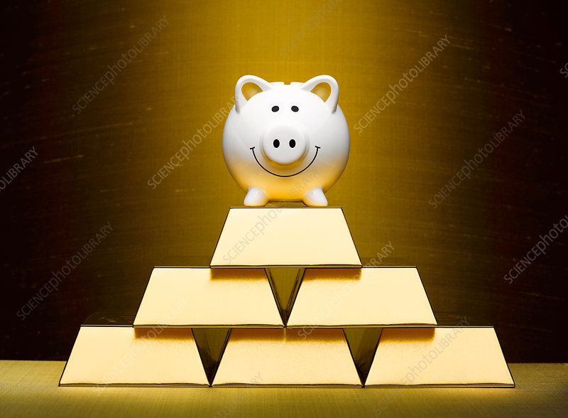 Smiling piggy bank on top of stacked gold bars