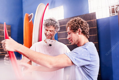 Men making and discussing surfboards in workshop