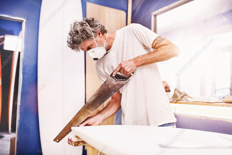 Male surfboard designer and using saw