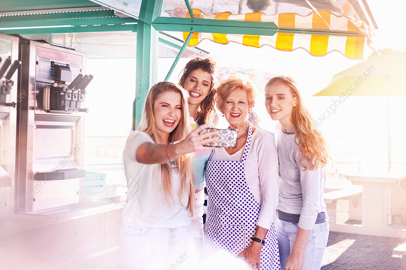 Young women taking selfie with business owner