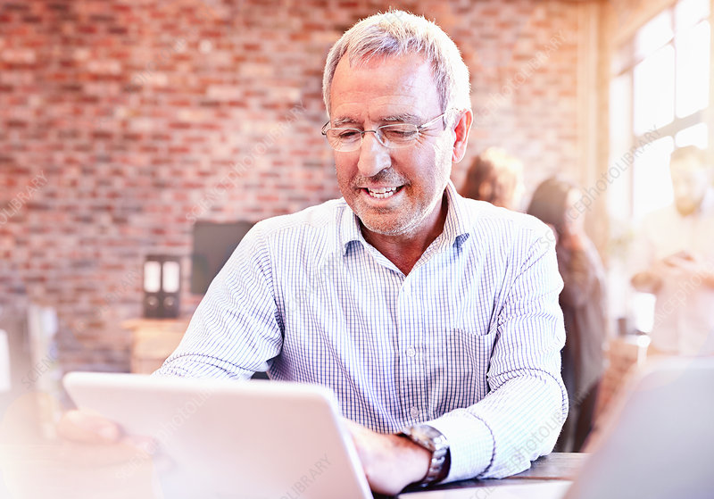 Smiling businessman using tablet in office