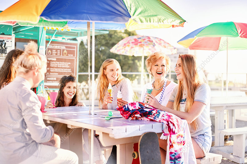 Happy women eating ice cream at picnic table