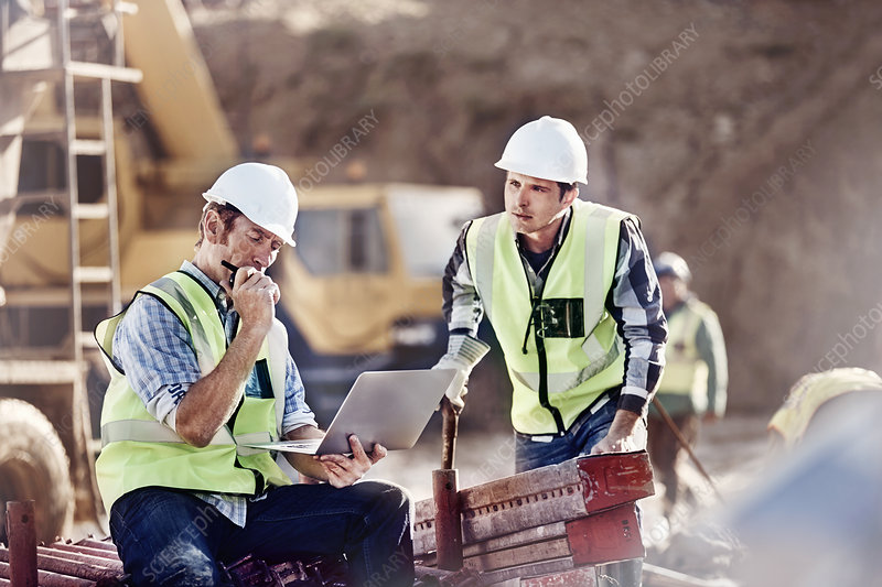 Foreman and construction worker using laptop