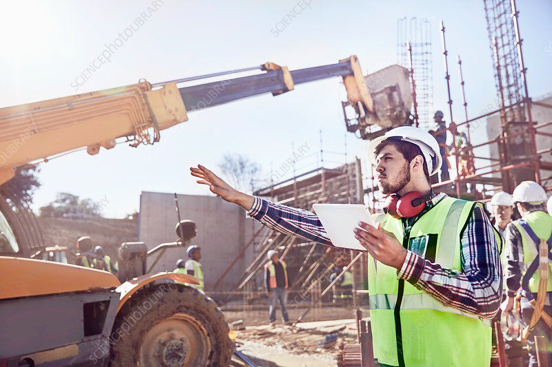 Construction worker with tablet guiding equipment