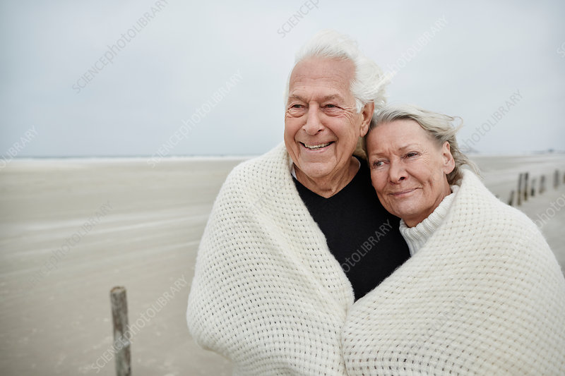 Senior couple wrapped in a blanket on beach