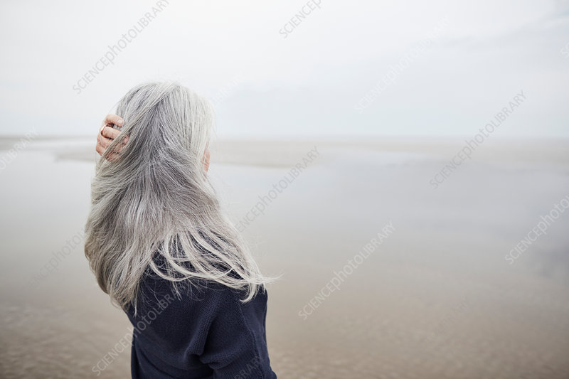 Senior woman with hand in long grey hair on beach